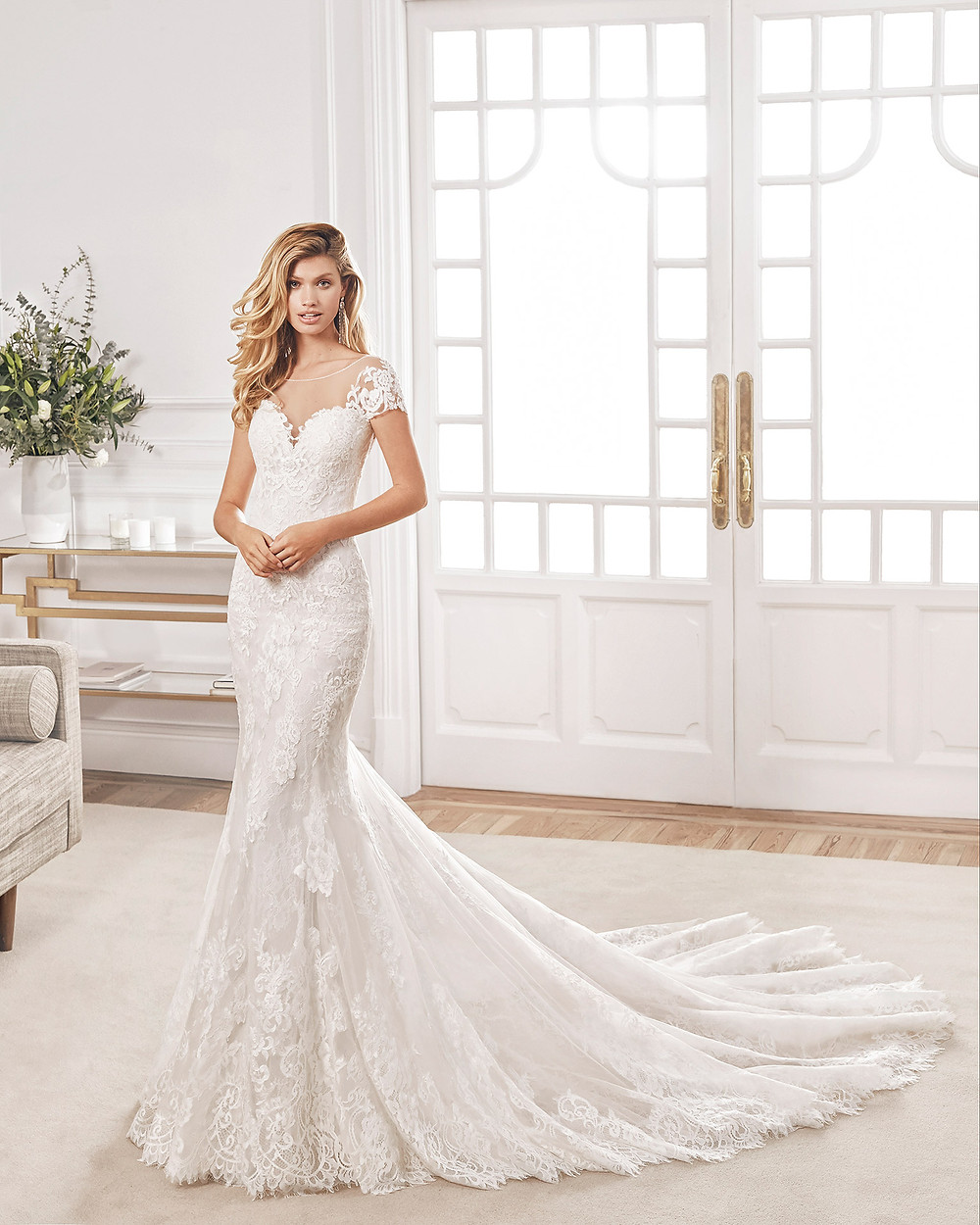 An Aire Barcelona 2020 lace mermaid fit and flare wedding dress with an illusion neckline
