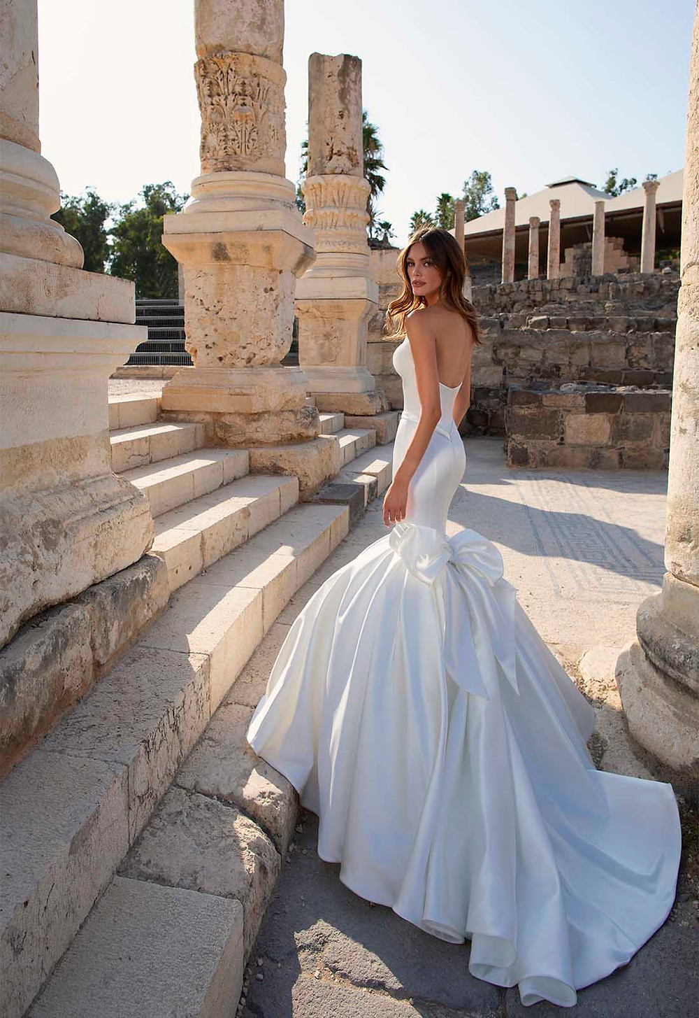 A Pnina Tornai strapless silk mermaid fit and flare wedding dress with a bow