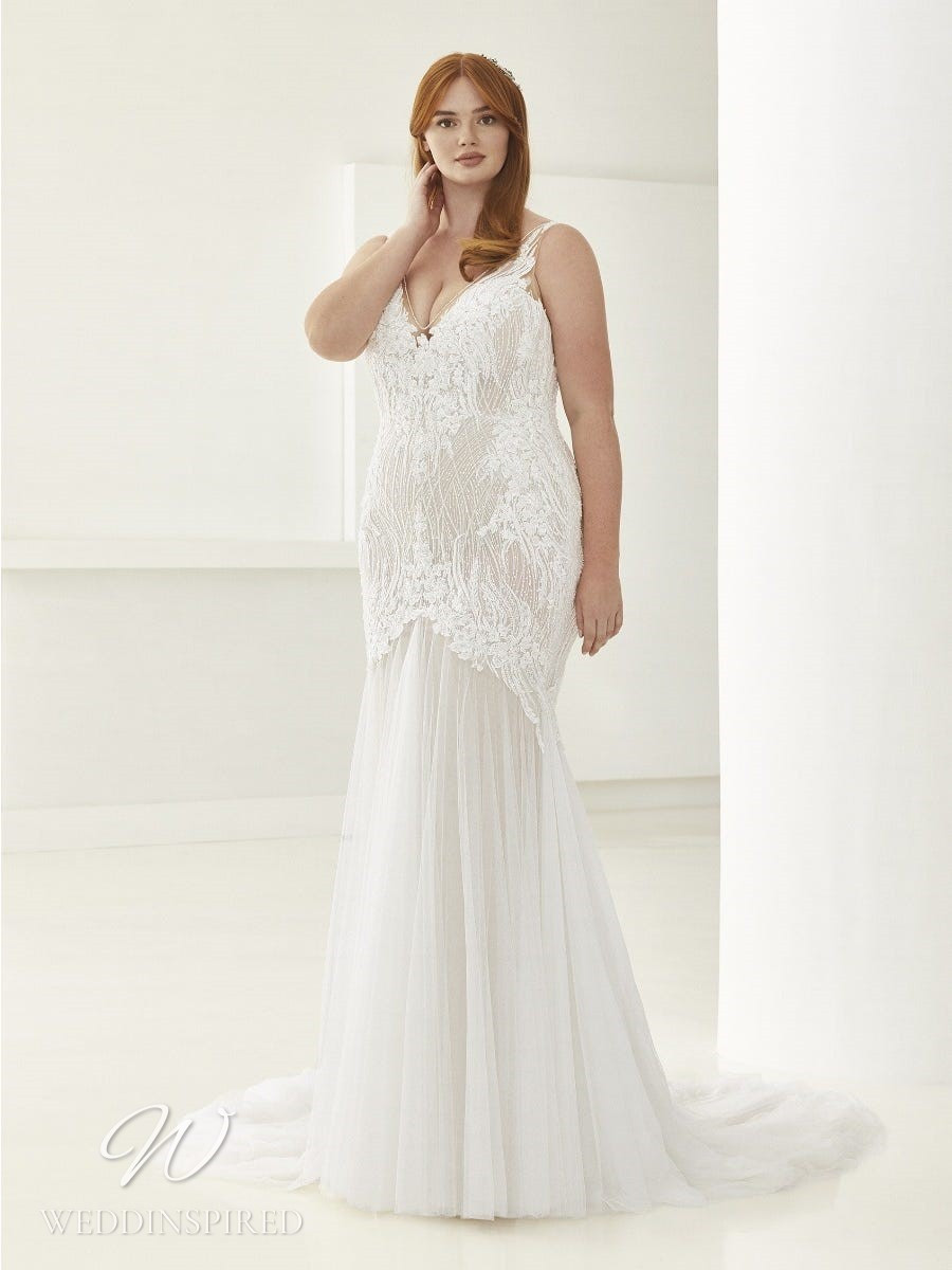 An Ashley Graham x Pronovias 2021 plus size lace and tulle mermaid wedding dress with a v neck and straps