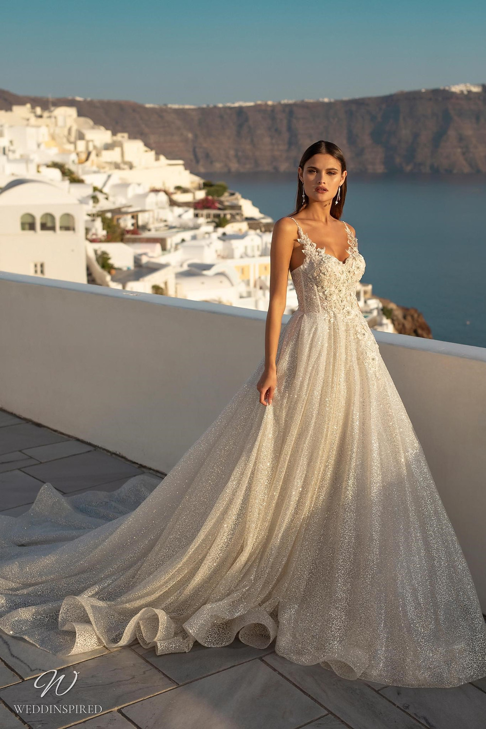 A Ricca Sposa sparkly ball gown wedding dress with lace straps and a train