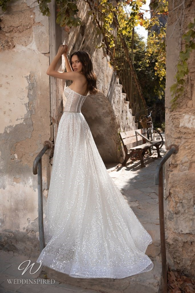 An Eden Aharon 2020 sparkly strapless tulle A-line wedding dress with a high slit and a bustier top