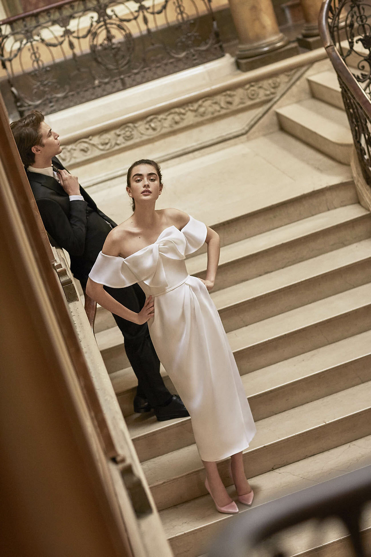 A Carolina Herrera off the shoulder silk tea length wedding dress with a bow