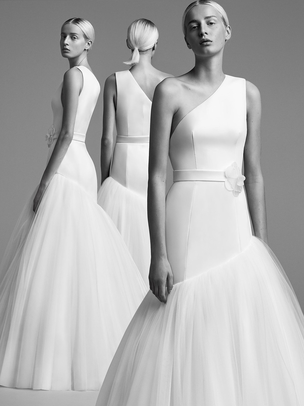 A one shoulder mermaid wedding dress with clean lines, a tulle skirt and a floral belt