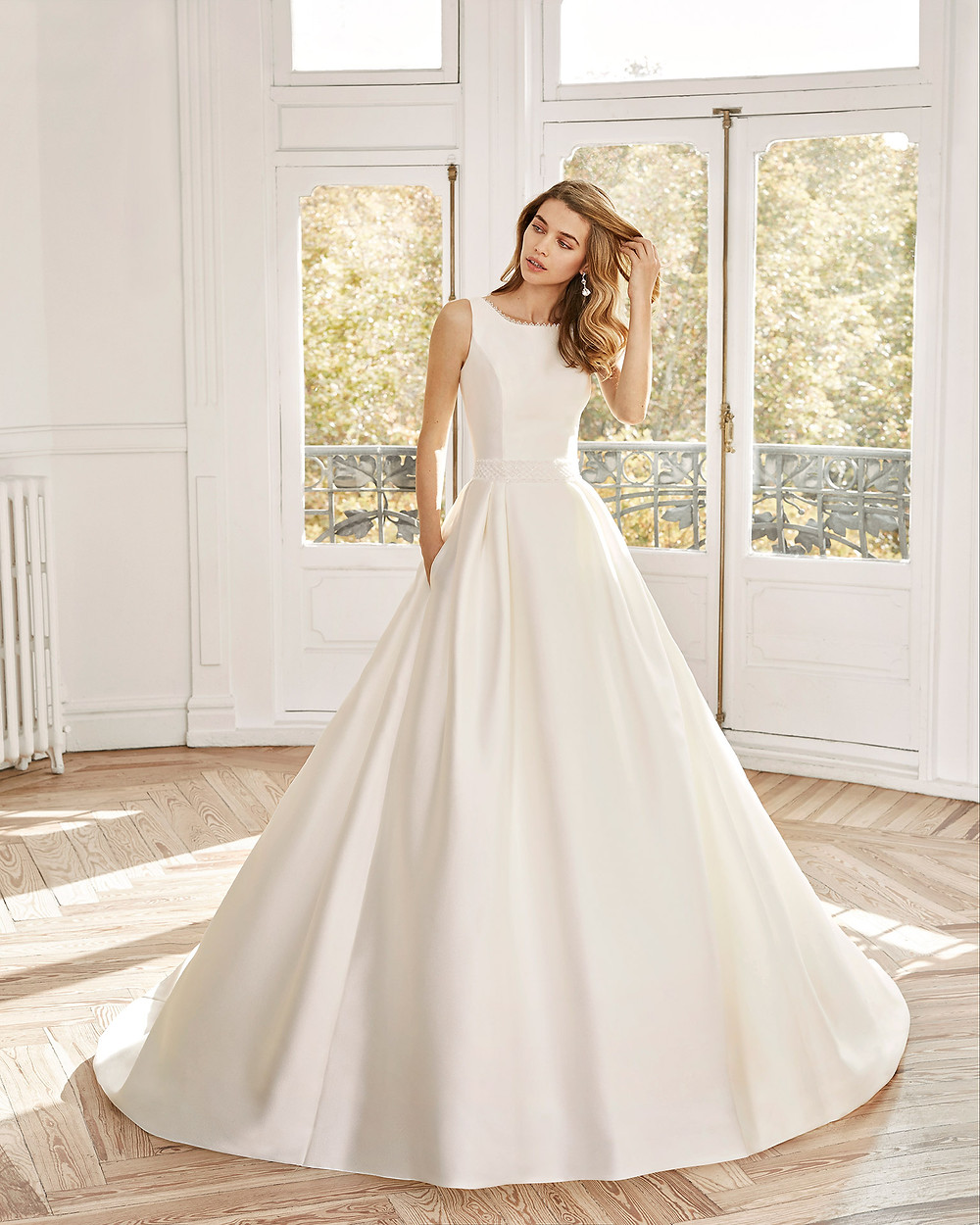 An Aire Barcelona 2020 simple silk ball gown wedding dress with pockets and a high neckline