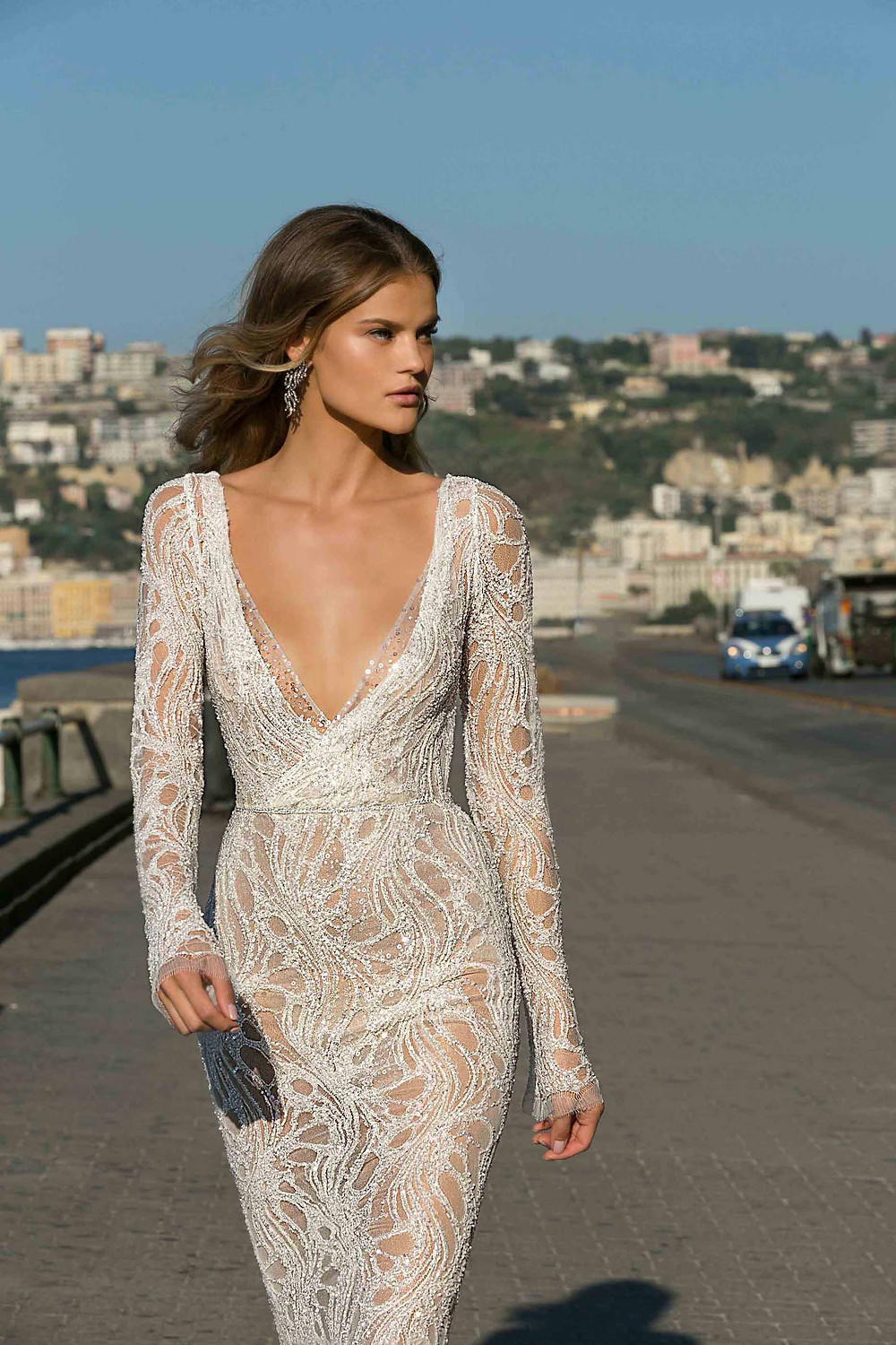 A sexy sheath wedding dress, with lace, a low v neckline and long sleeves