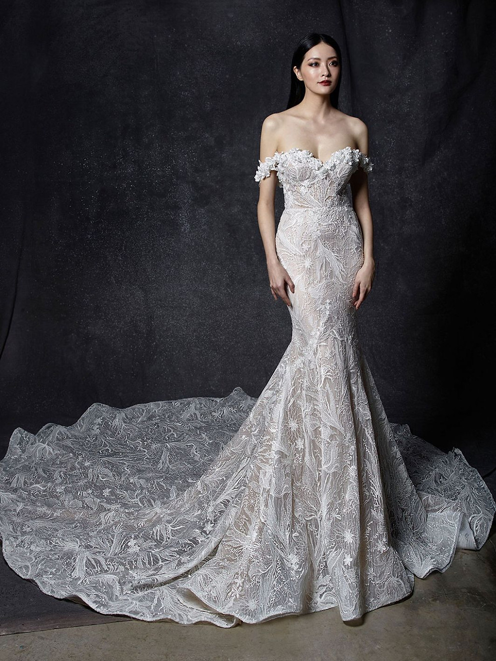 An Enzoani off the shoulder lace mermaid wedding dress with a sweetheart neckline and a long train