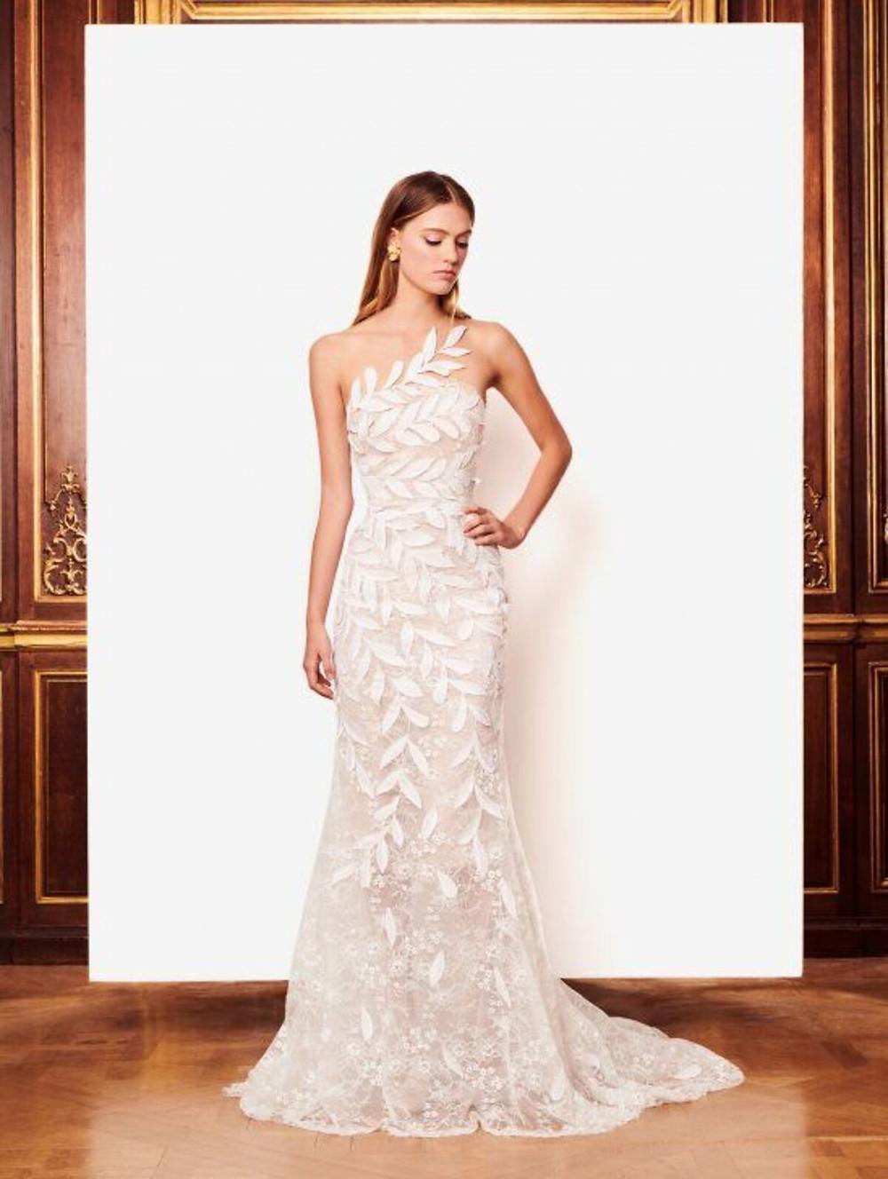 A one shoulder, mermaid wedding dress with leaf print and embellishments