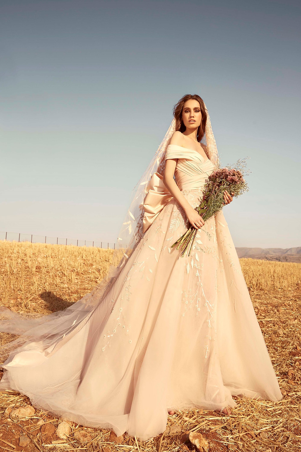 A Zuhair Murad off the shoulder blush silk and tulle ball gown wedding dress with a bow
