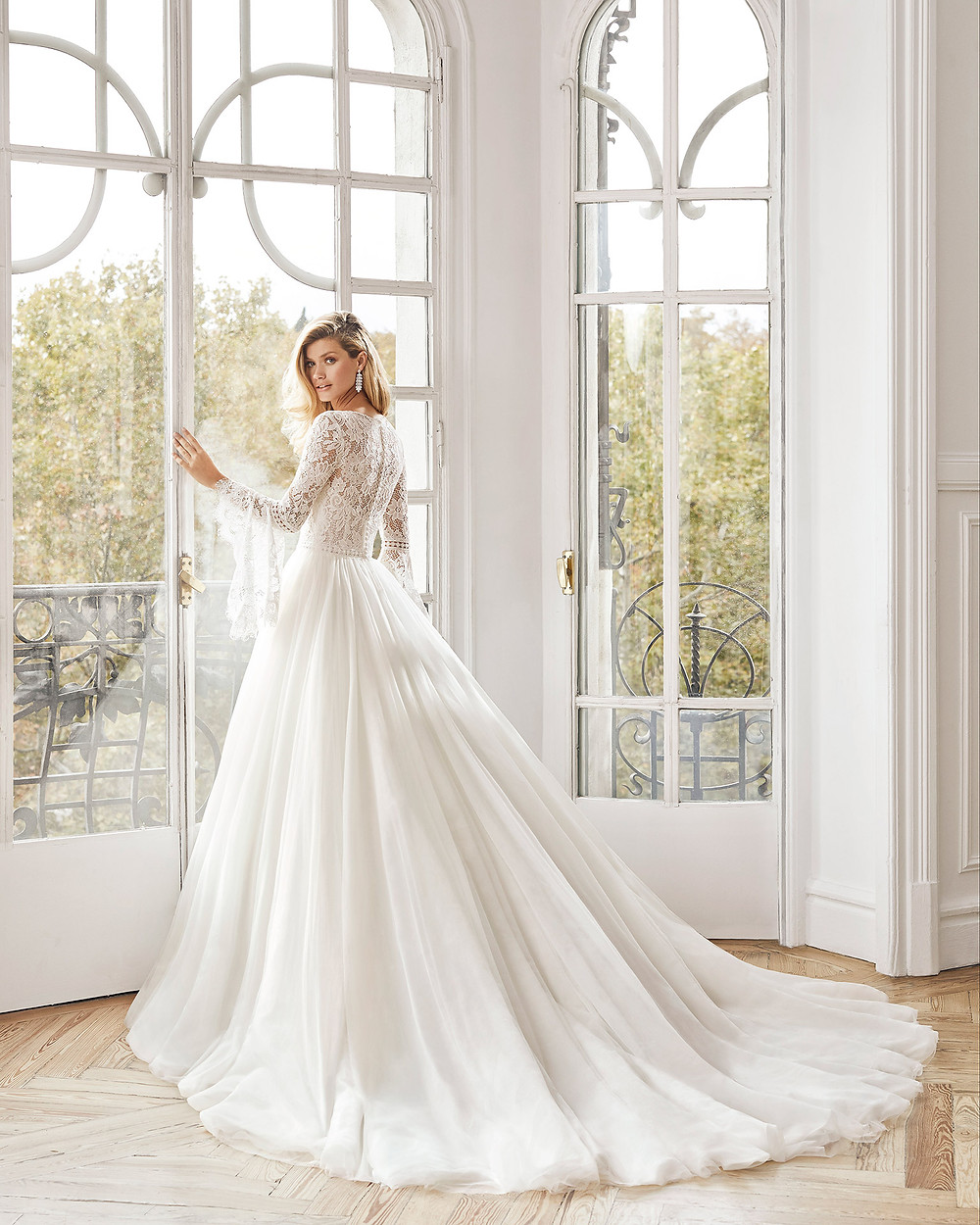An Aire Barcelona 2020 modest lace and tulle ball gown wedding dress with long sleeves and a high neckline