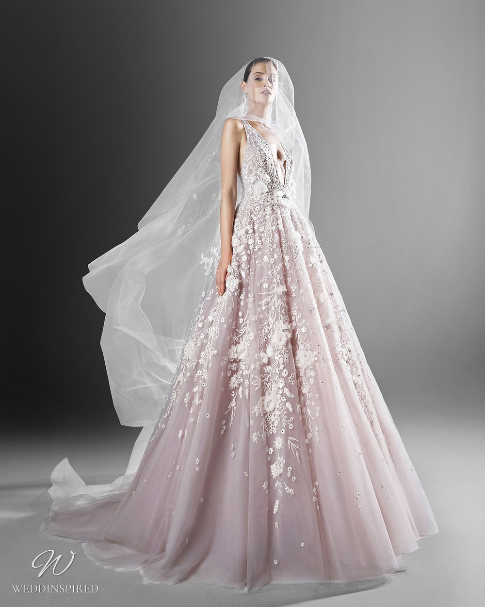 A Zuhair Murad romantic blush princess ball gown wedding dress with a tulle skirt, flowers and a veil