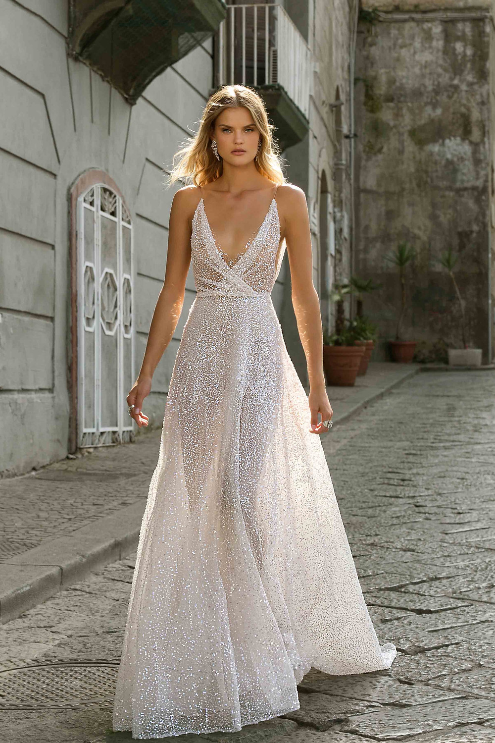 A sparkly A-line wedding dress, with deep v neckline, thin straps and crystals