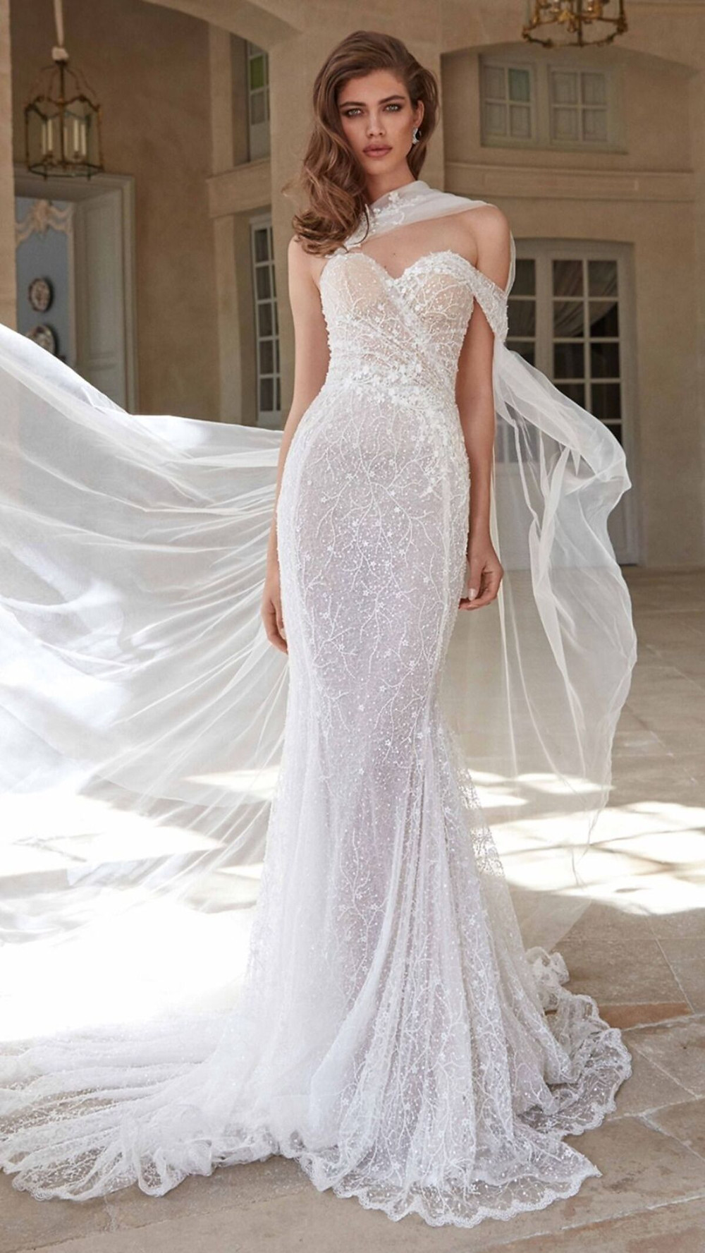 This soft mermaid wedding gown artfully draped with a delicate silk tulle and embroidered with scattered pearls and shimmery sequins features a sweetheart neckline, flowing skirt, and a sheer cape that attaches to the sweetheart neckline
