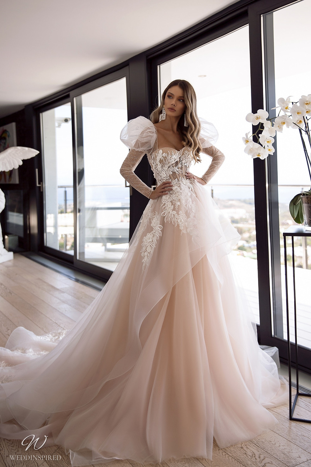 A Tina Valerdi romantic blush princess ball gown wedding dress with a tulle skirt and long sleeves