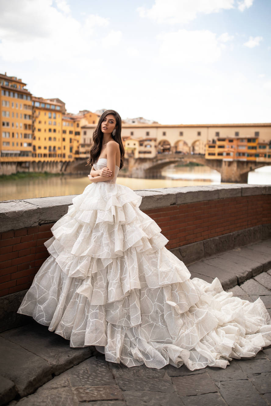 A Milla Nova strapless ball gown wedding dress with a layered skirt and a sweetheart neckline