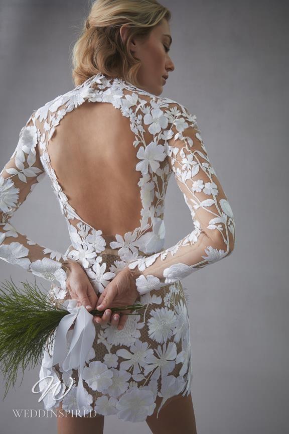 An Oscar de la Renta 2022 short lace wedding dress with a keyhole back and long sleeves