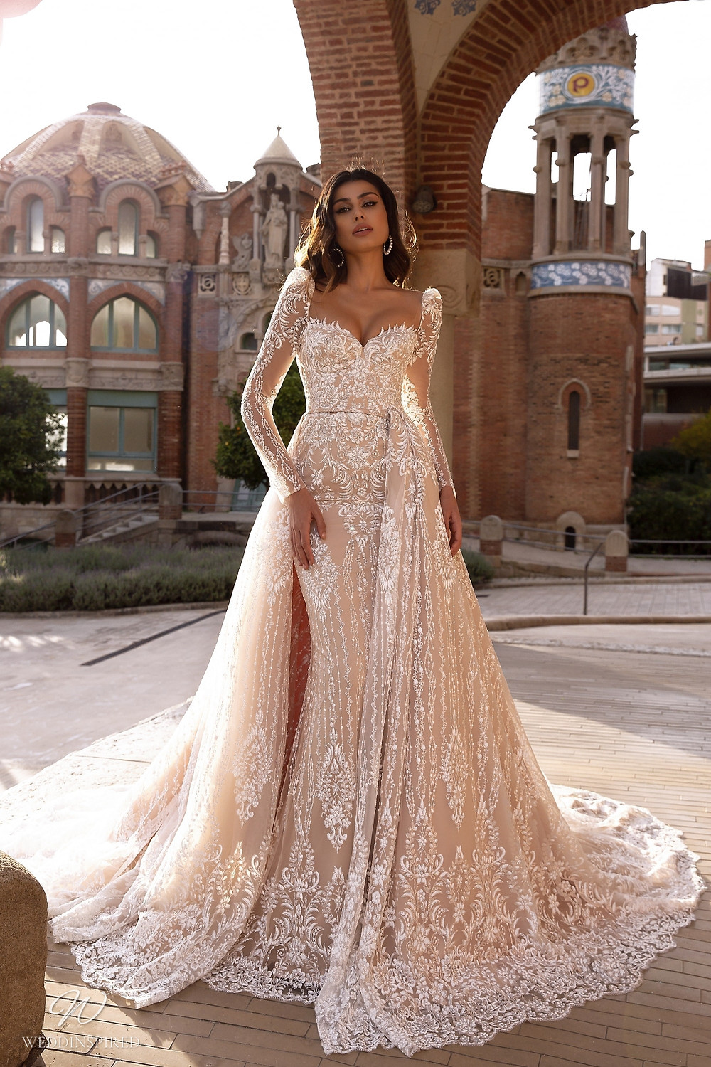 A Maks Mariano blush lace mermaid wedding dress with a detachable skirt and long sleeves