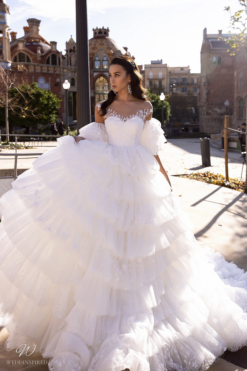 A Maks Mariano off the shoulder princess ball gown wedding dress with layered ruffle skirt