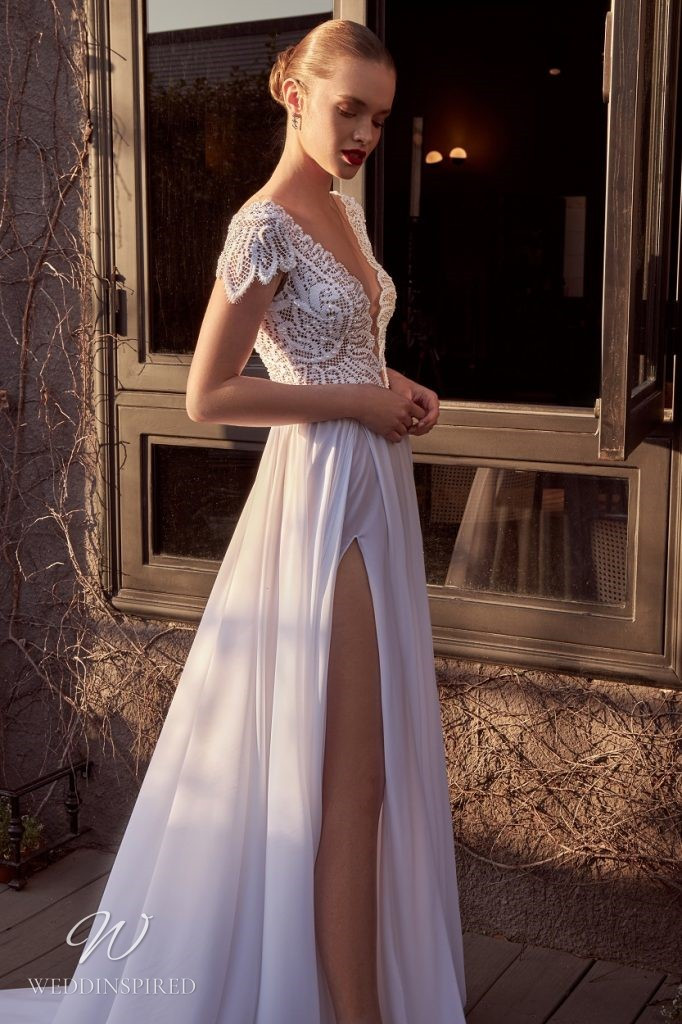 A Julie Vino 2021 crepe and lace A-line wedding dress with cap sleeves and a high slit