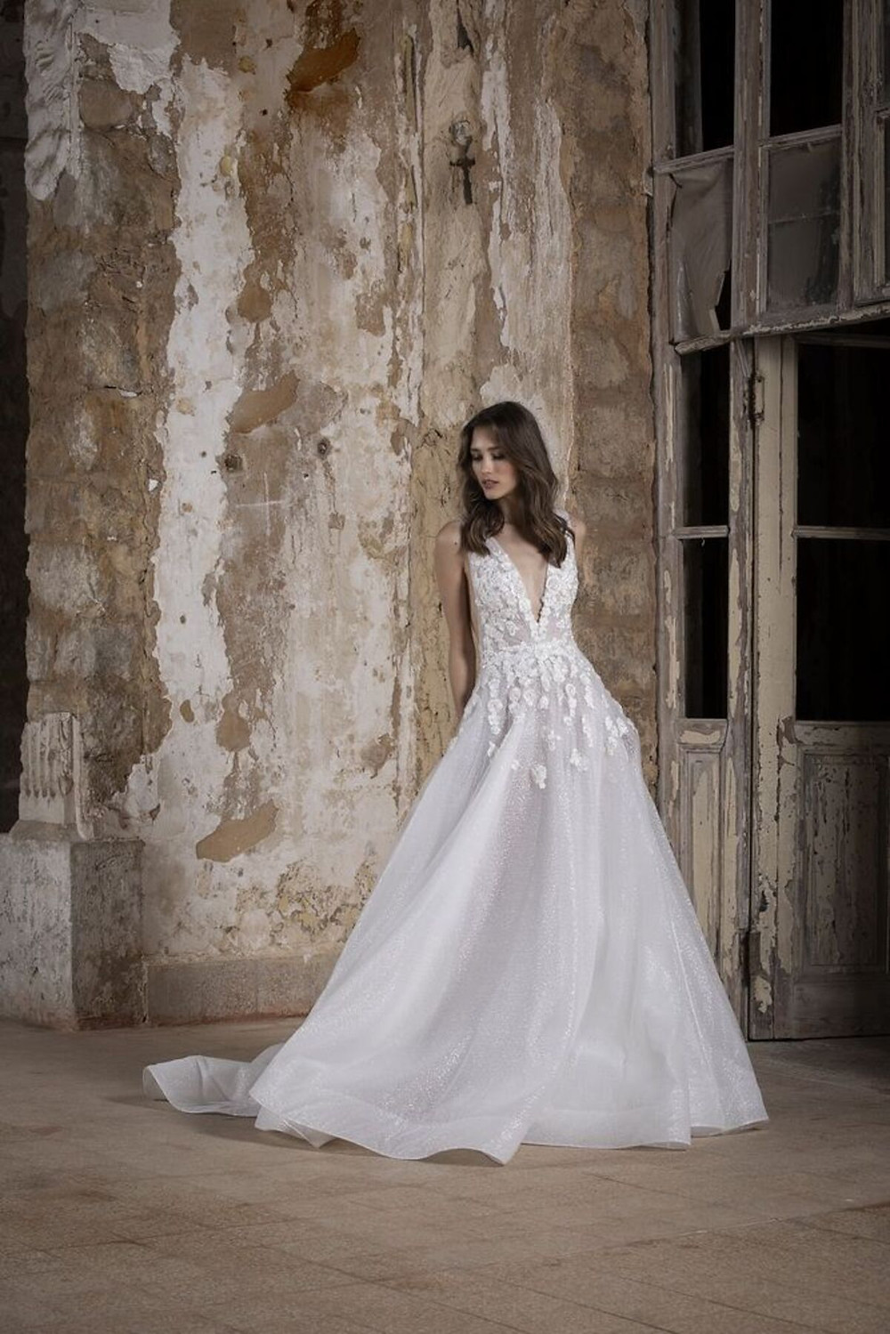 An A-line wedding dress made of embroidered tulle and cascading silk flowers