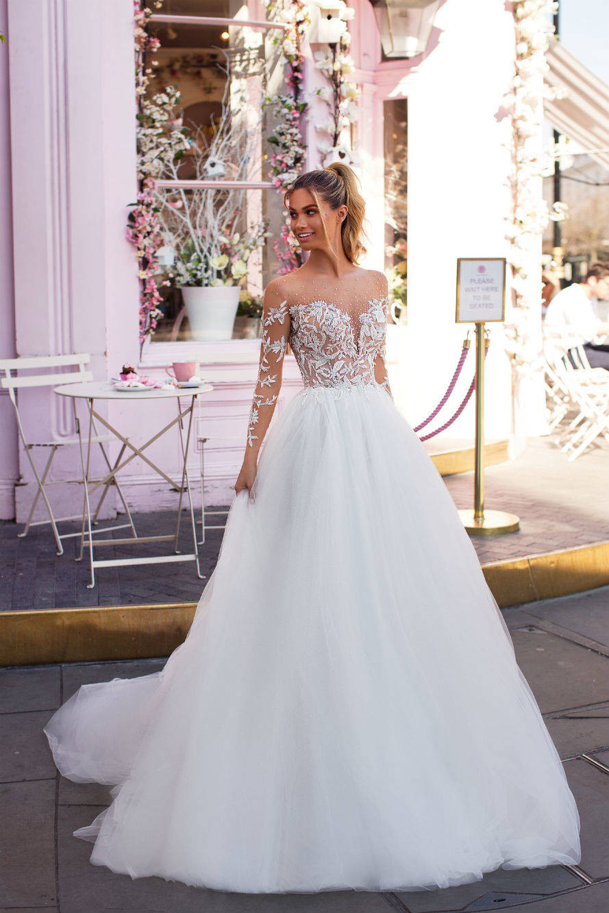 An off the shoulder, ball gown wedding dress, with tulle skirt, lace bodice, long sleeves and pearls