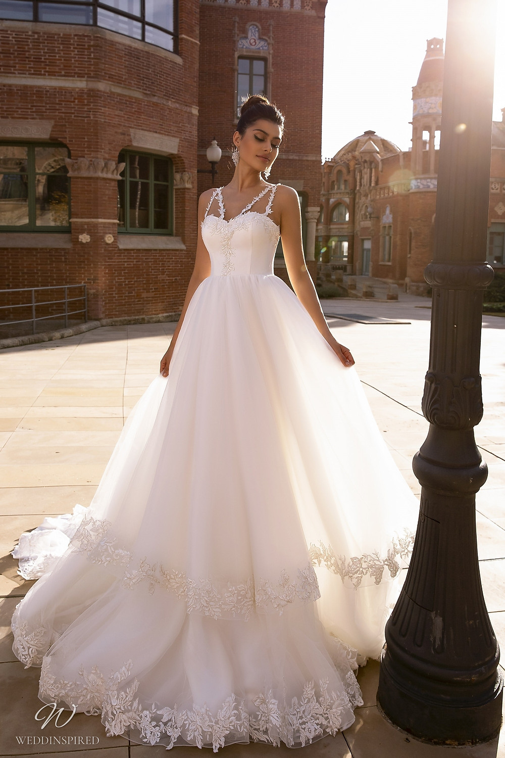 A Maks Mariano princess ball gown wedding dress with layered tulle ruffle skirt