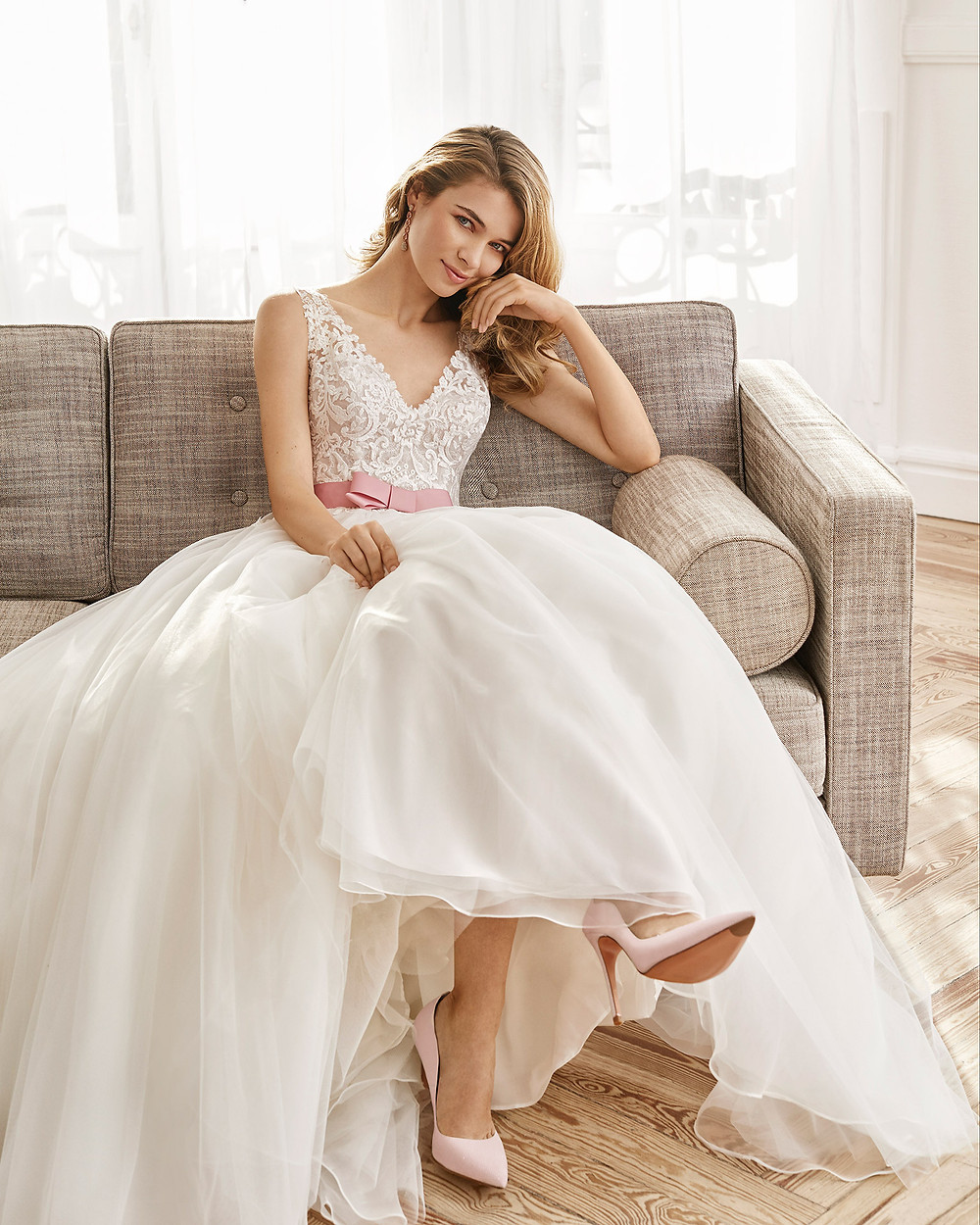 An Aire Barcelona 2020 lace and chiffon ball gown wedding dress with a pink bow