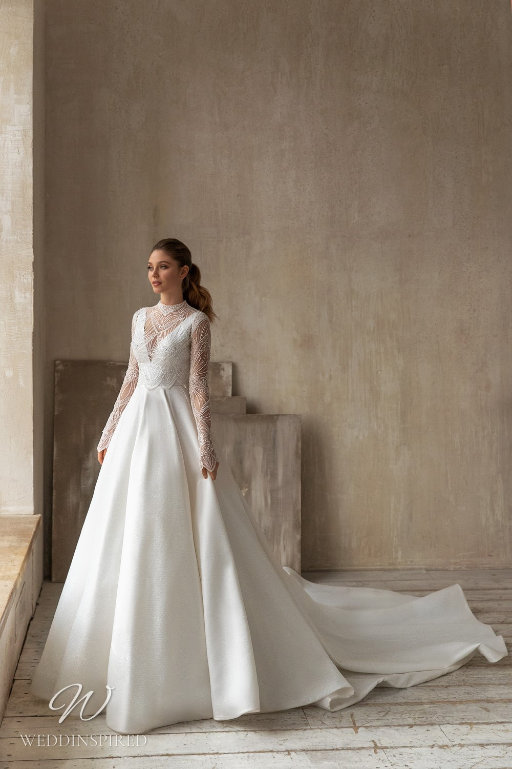 An Eva Lendel 2021 crepe and mesh ball gown wedding dress with long illusion sleeves and a train