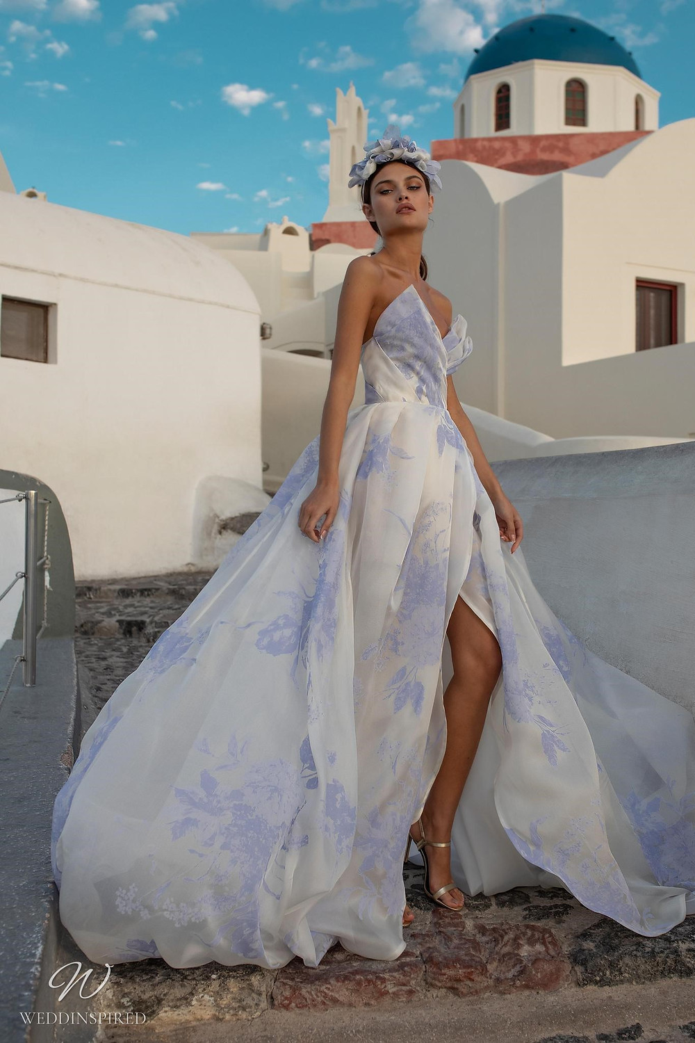 A Ricca Sposa strapless chiffon ball gown wedding dress with blue flowers and a high slit