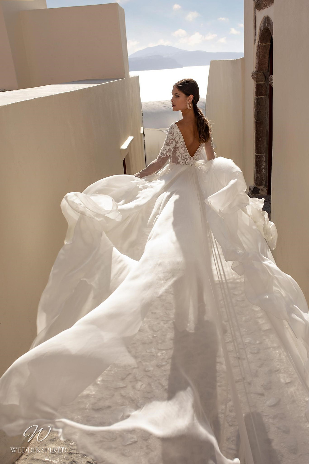 A Ricca Sposa soft flowy ball gown wedding dress with a lace top, long sleeves and a low back