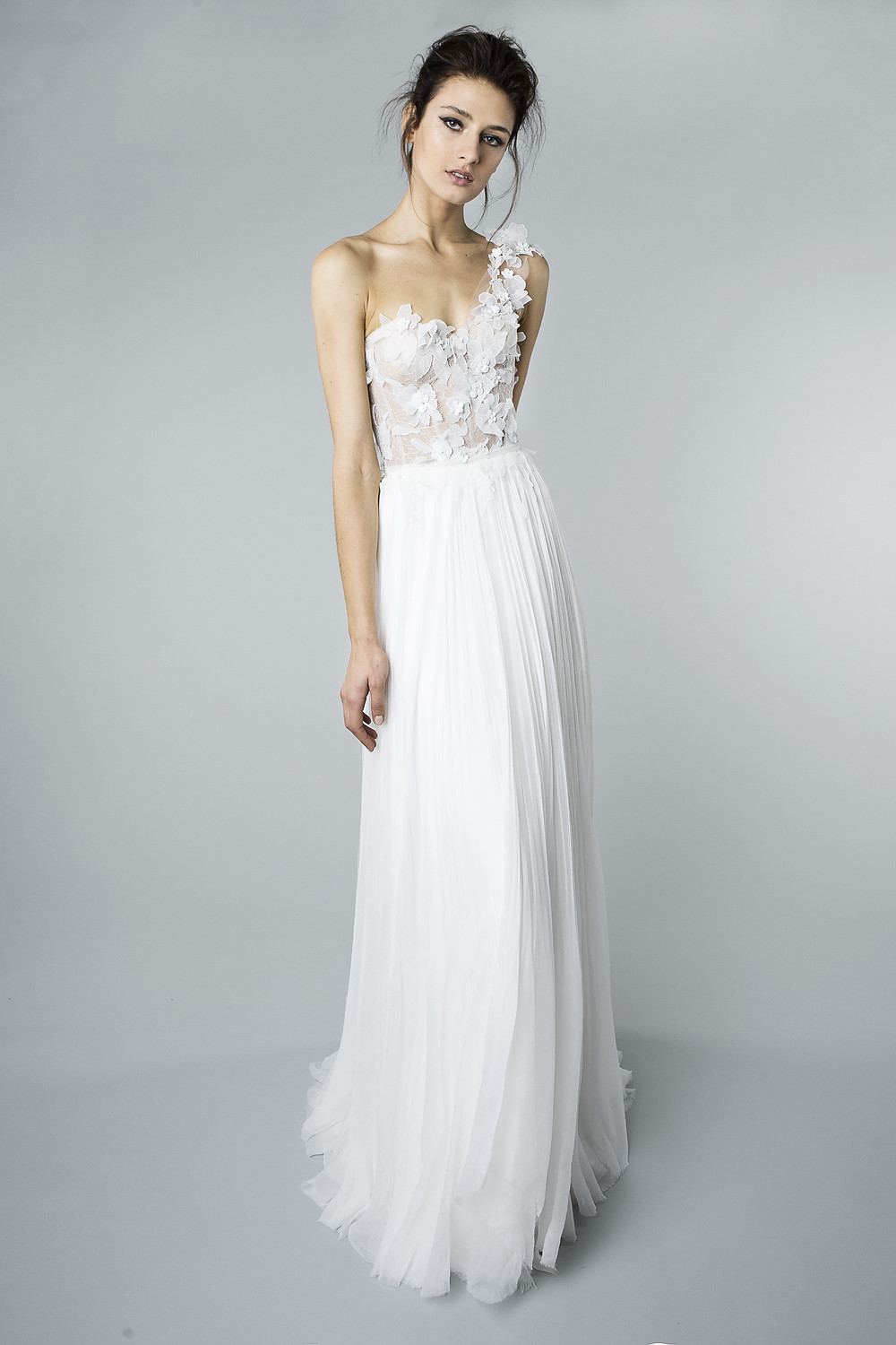 A Mira Zwillinger one shoulder, sheath wedding dress with pleated skirt and flowers