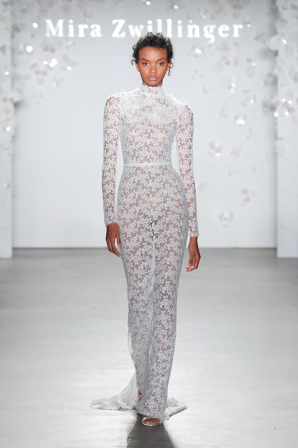A Mira Zwillinger fitted lace wedding dress with long sleeves and a high neckline
