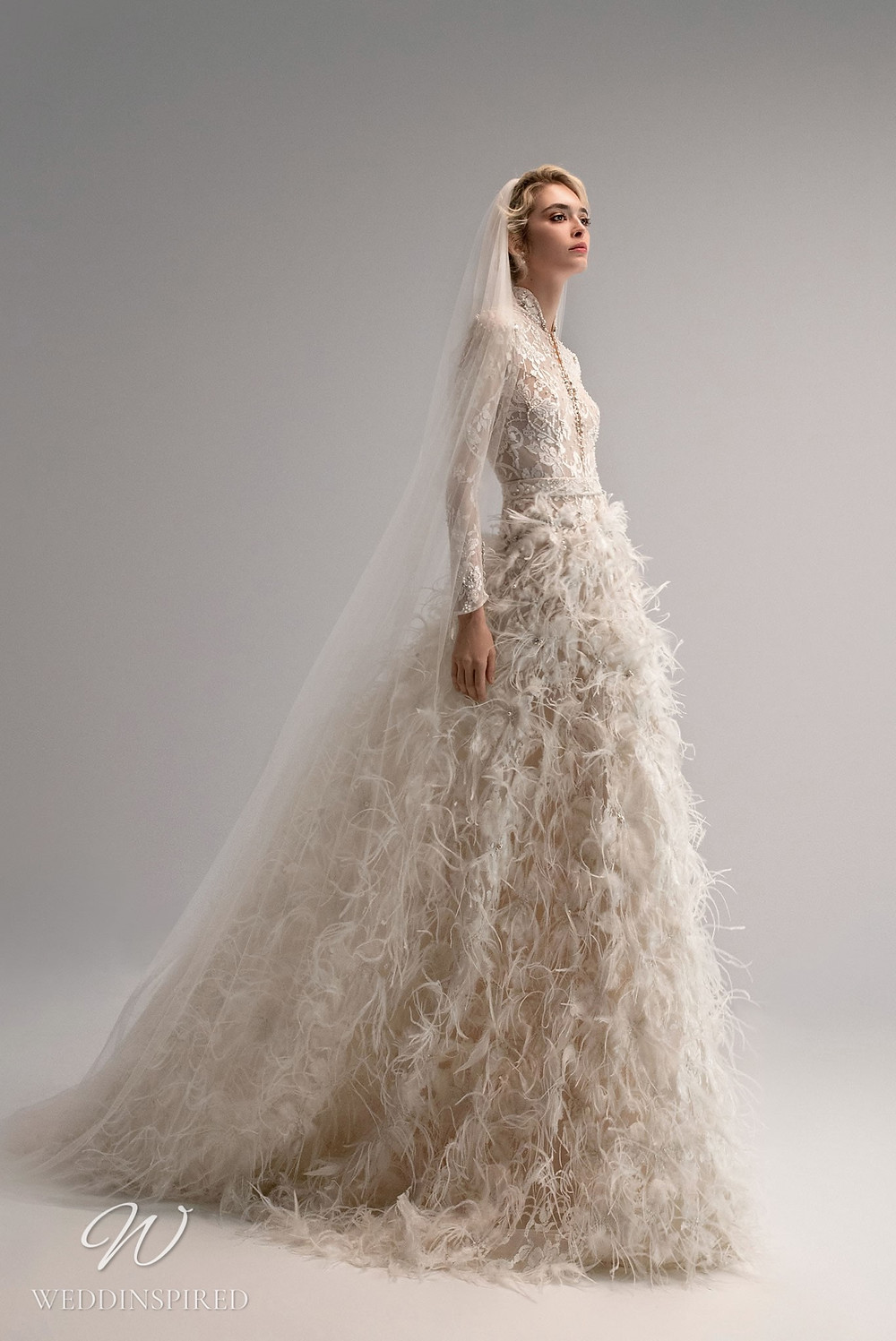 An Ersa Atelier 2021 feather ball gown wedding dress with a lace bodice and long sleeves