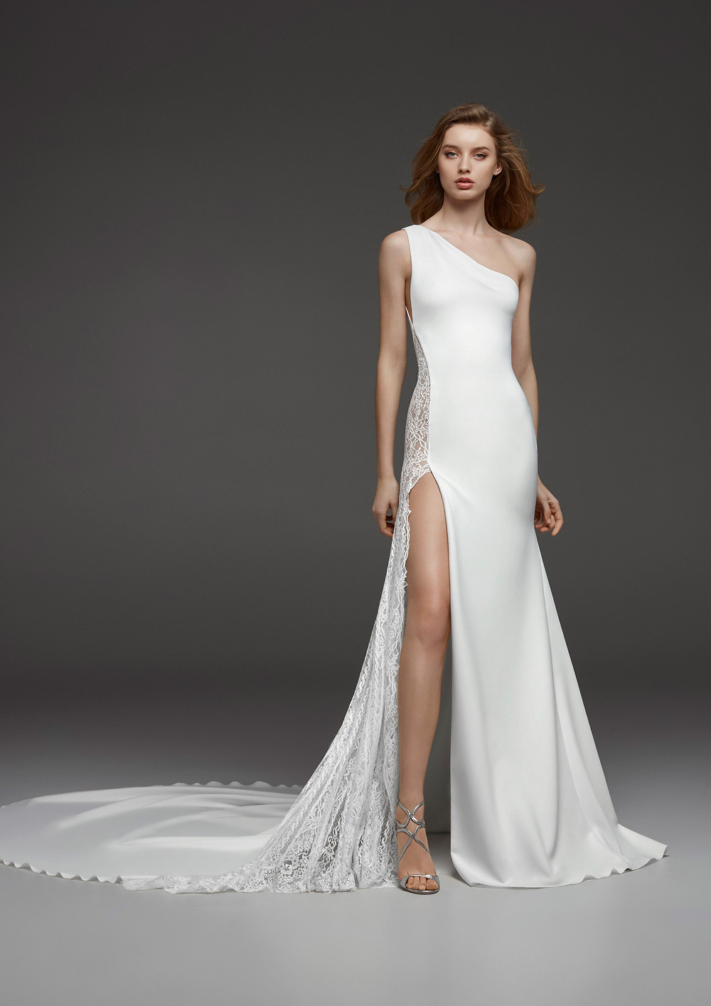 A Pronovias one shoulder, sheath wedding dress, with lace insert