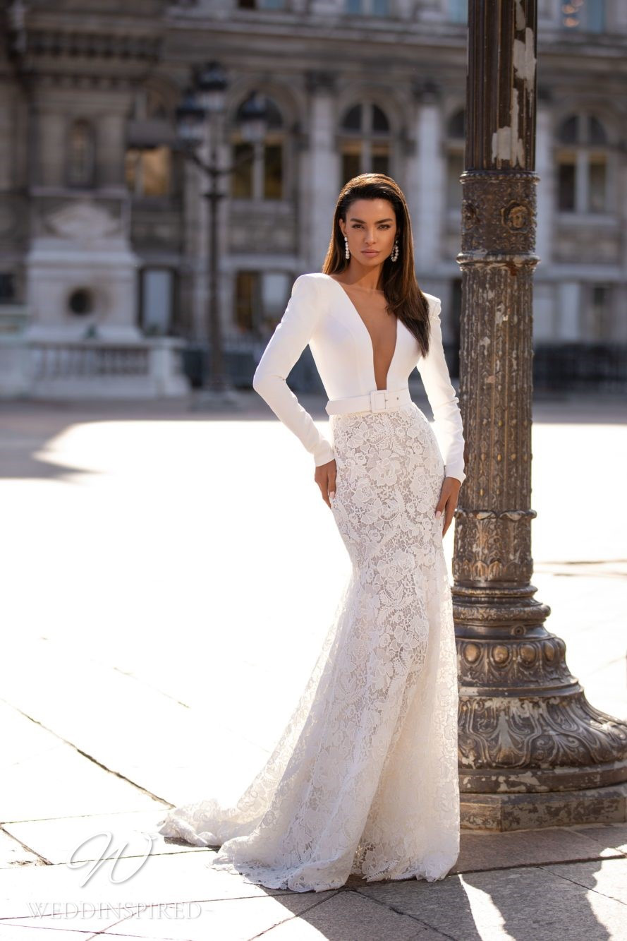 A Milla Nova lace mermaid wedding dress with long sleeves, a belt and a low v neckline