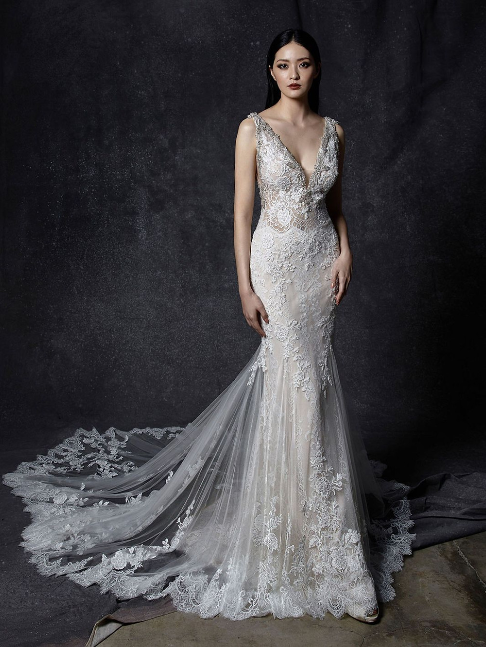An Enzoani v neck, lace mermaid wedding dress with a long train