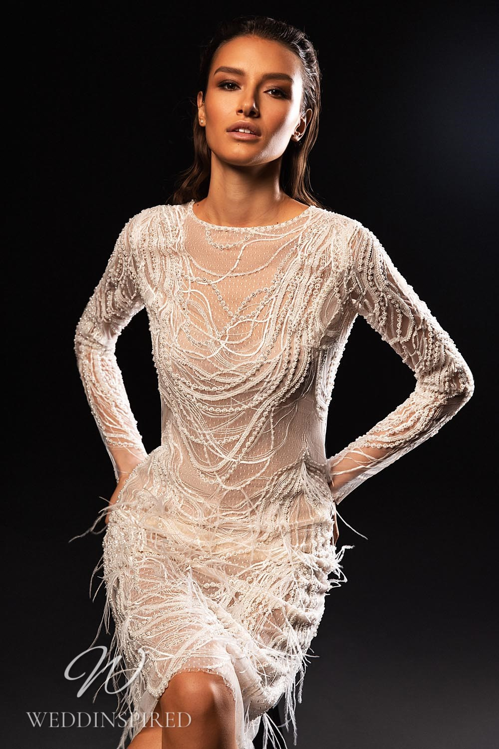 A WONÁ Concept 2021 short wedding dress with feathers and long sleeves