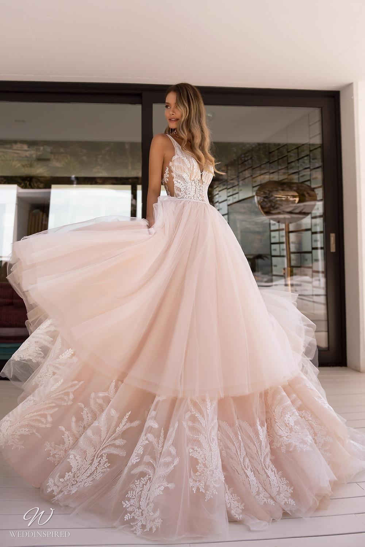 A Tina Valerdi romantic blush tulle ball gown wedding dress with a layered ruffle skirt