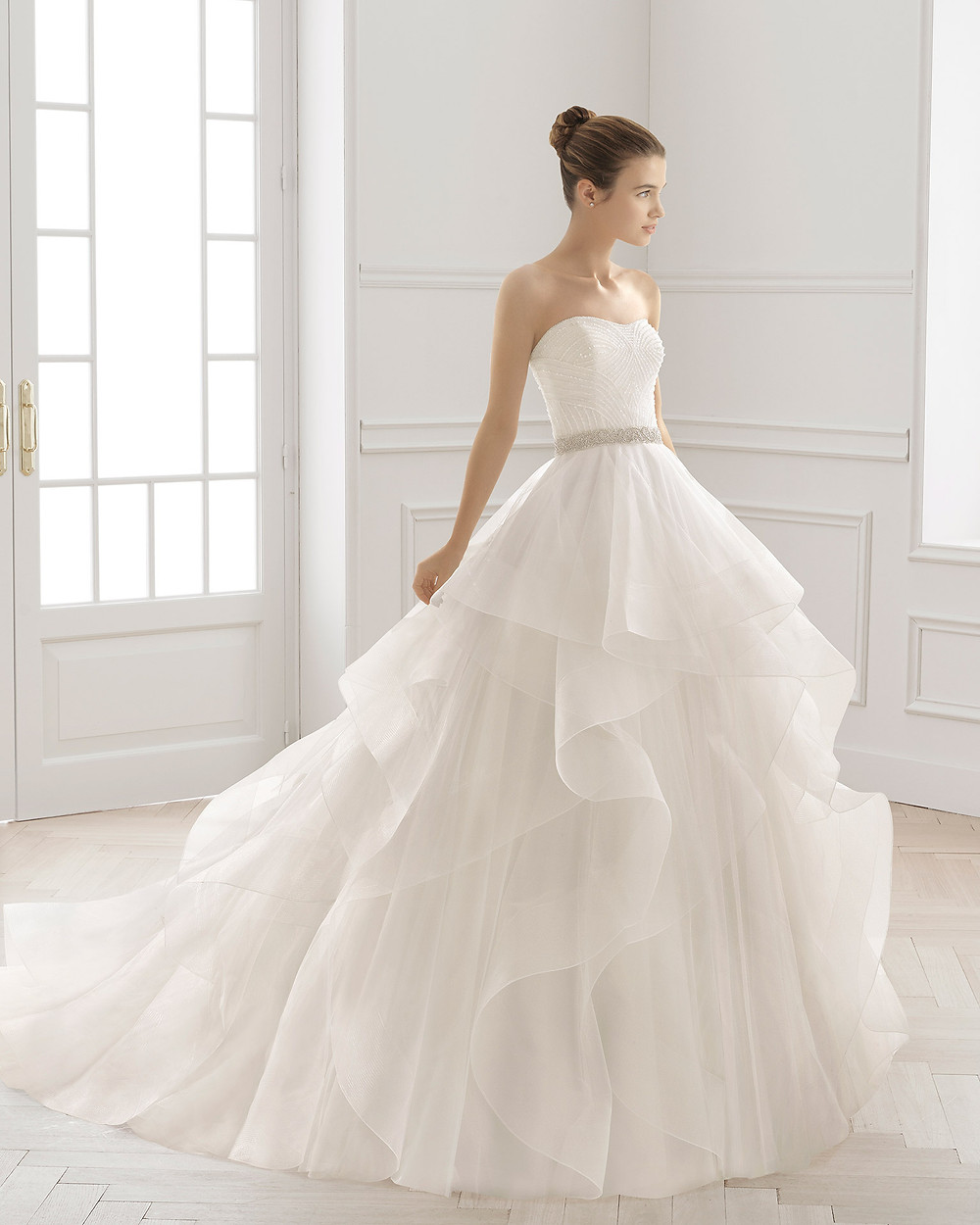 An Aire Barcelona 2020 strapless ball gown wedding dress with a tulle layered ruffle skirt
