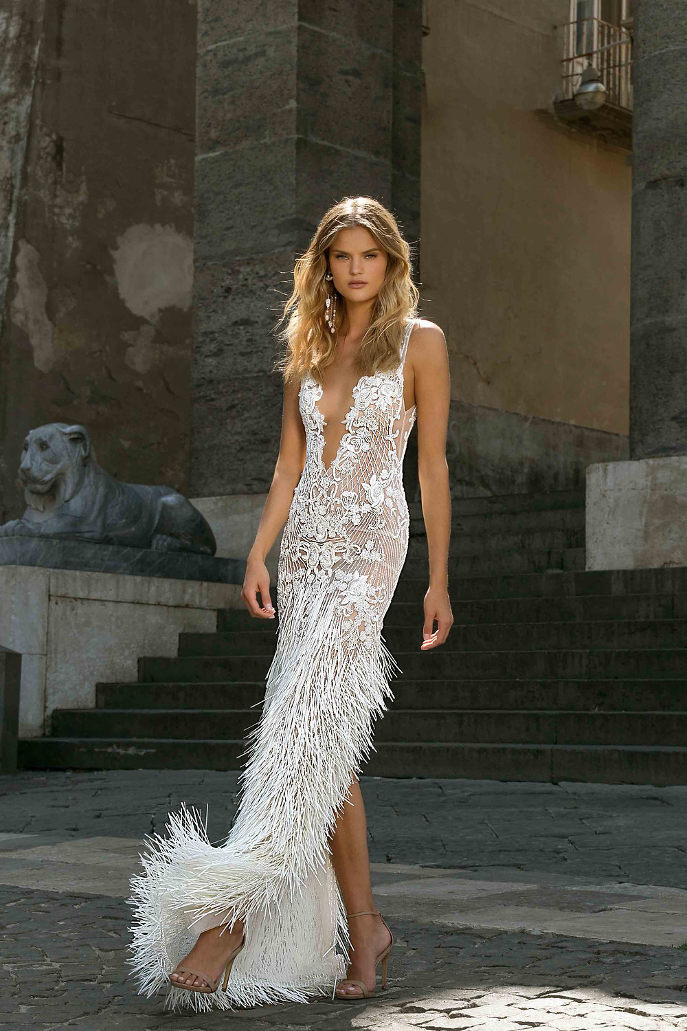 A sexy wedding dress with a high slit, lace, feathers, thin straps and a low v neckline