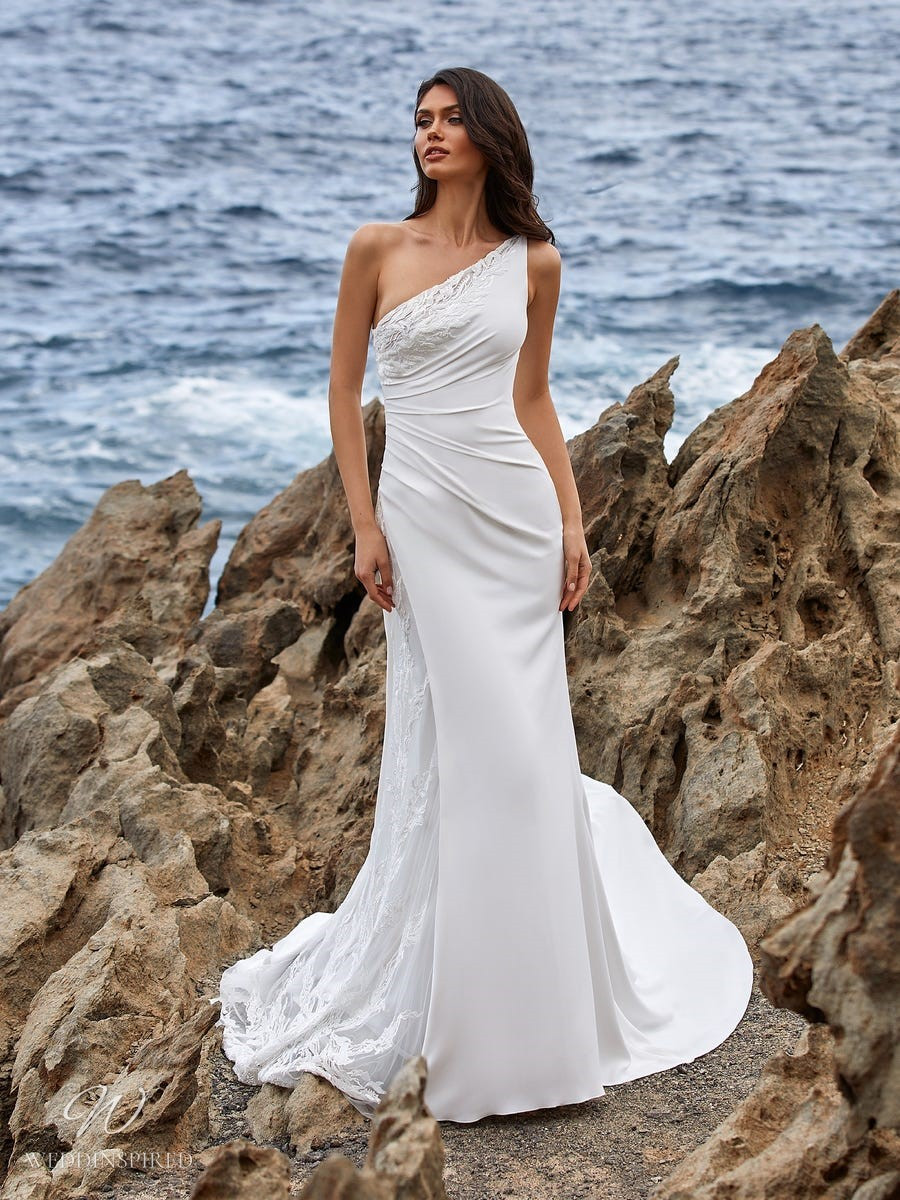 A Pronovias 2021 Grecian style one shoulder simple mermaid wedding dress with lace inserts