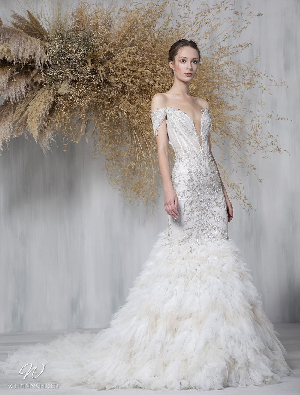 A Tony Ward 2021 off the shoulder mermaid wedding dress with a ruffle skirt and a v neckline