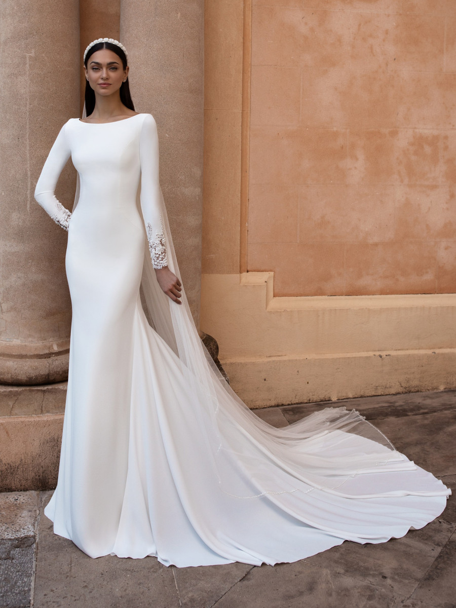 A Pronovias simple modest fitted wedding dress with long sleeves and a train