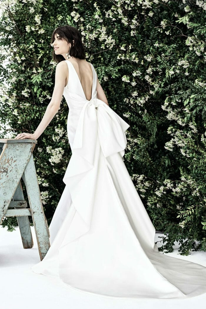 A Carolina Herrera crepe mermaid fit and flare wedding dress with a low back and a bow