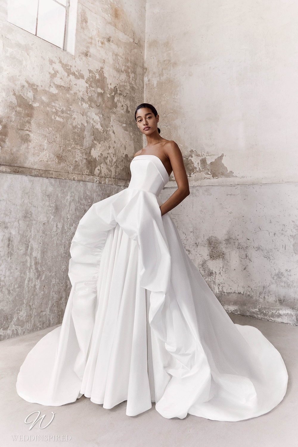 A Viktor & Rolf Fall/Winter 2021 simple strapless ball gown wedding dress with a layered ruffle skirt