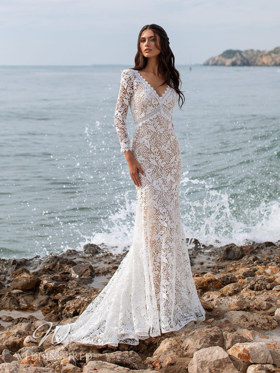 An Ashley Graham x Pronovias 2021 intricate lace mermaid wedding dress with a v neck and long sleeves