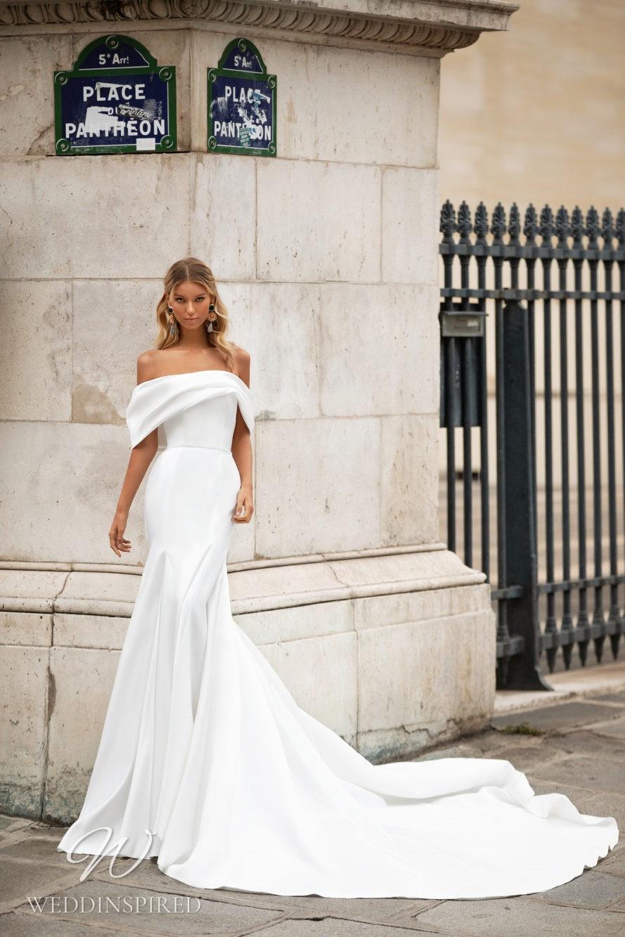 A Milla Nova white off the shoulder mermaid wedding dress with a train