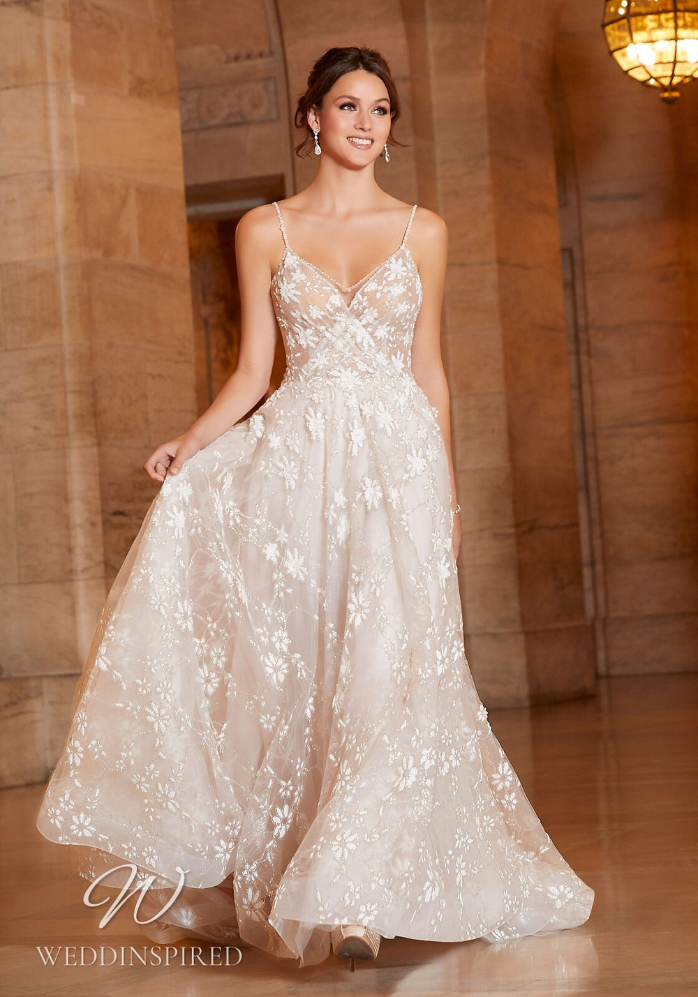 A Madeline Gardner lace A-line wedding dress with a v neck and straps