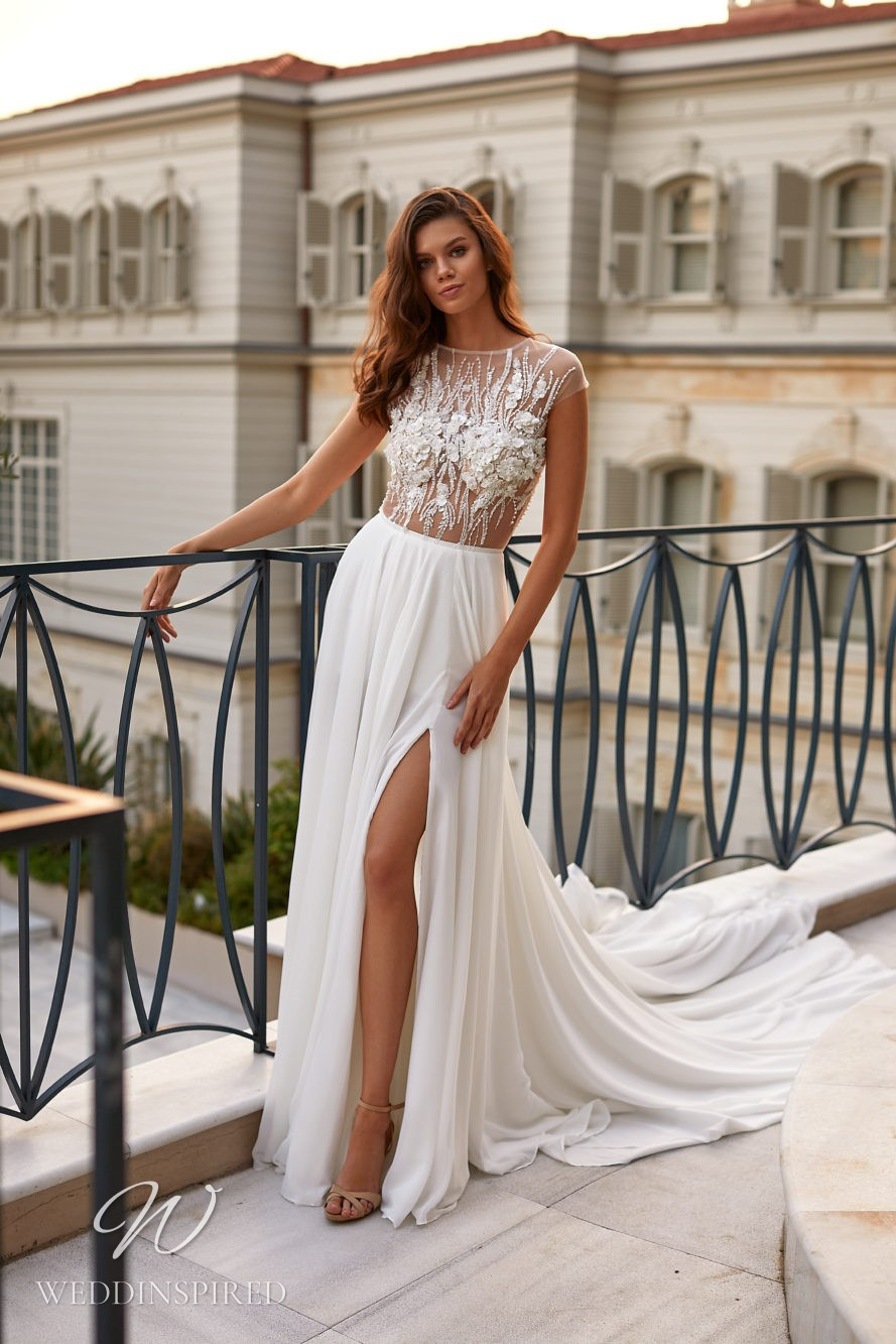 A Milla Nova 2021 chiffon and beaded A-line wedding dress with an illusion top and cap sleeves