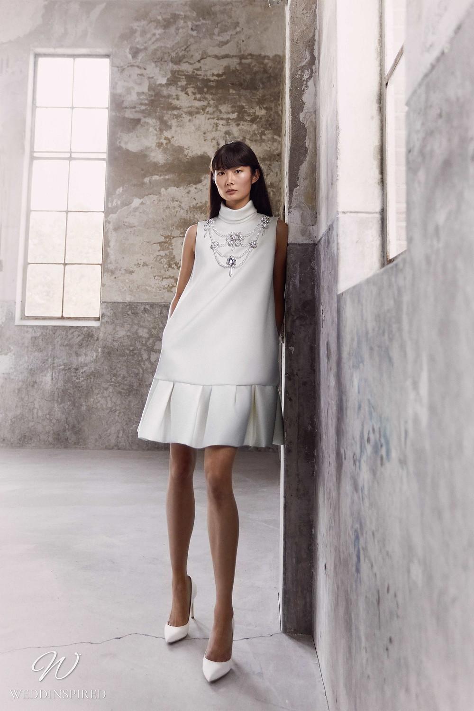 A Viktor & Rolf Fall/Winter 2021 simple short wedding dress with a high neckline