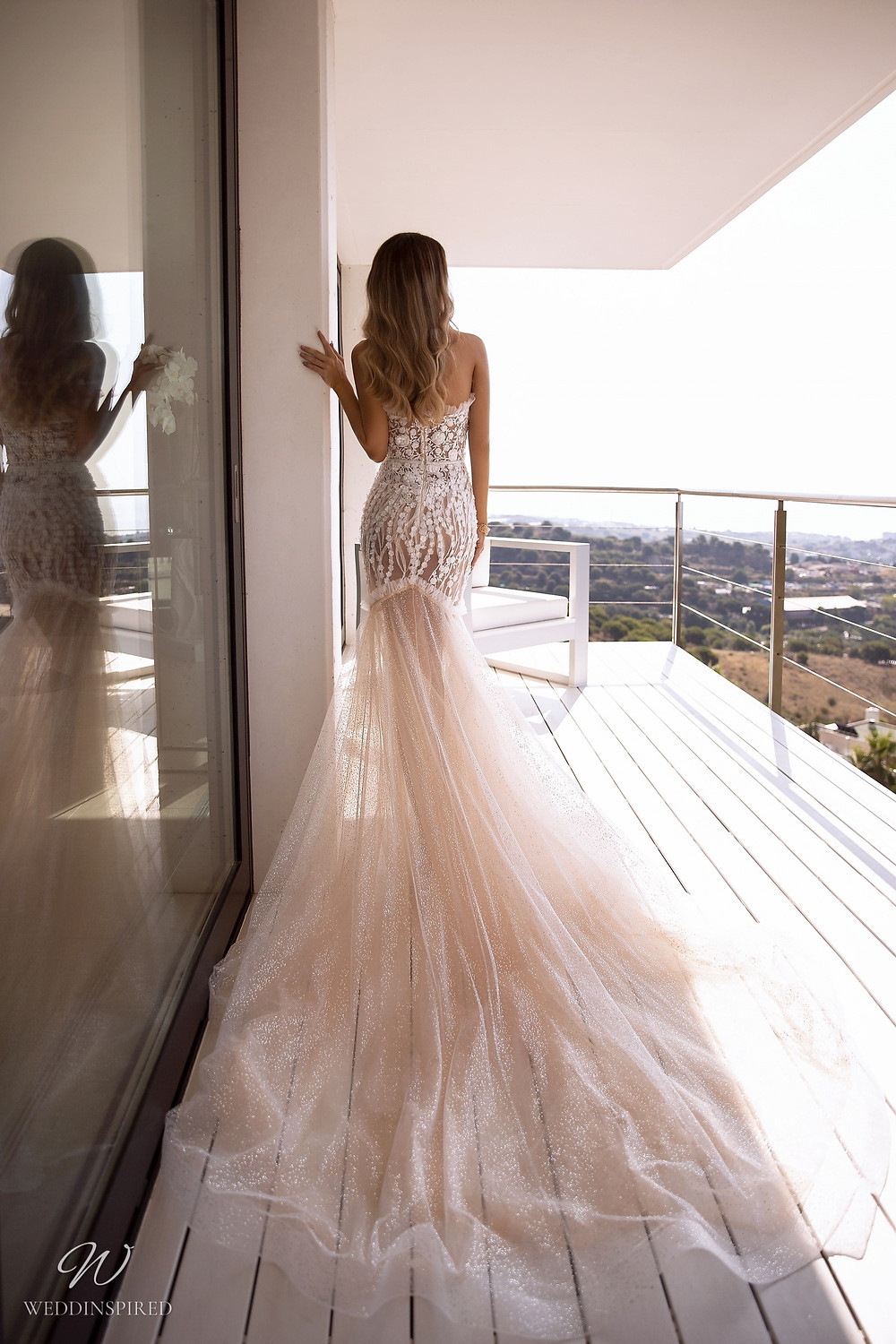 A Tina Valerdi blush mermaid wedding dress with a lace bodice and tulle skirt